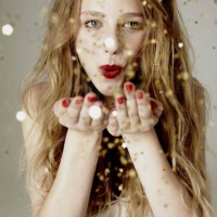 girl blowing gold glitter