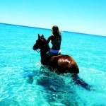 Girl riding a horse in the sea